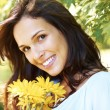 Cute young girl with yellow flowers smiling - Stock Photo