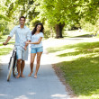Royalty-Free Stock Photo: Happy couple walking with bicycle in a park