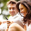 Royalty-Free Stock Photo: Pretty young woman using mobile with her boyfriend in background