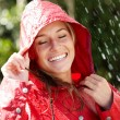 Portrait of smiling teenage girl enjoying the rain - Stock Photo