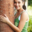 Royalty-Free Stock Photo: Pretty young woman hugging a big tree in a park