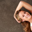 Closeup of an attractive young woman lying on floor - Stok fotoraf