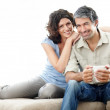 Royalty-Free Stock Photo: Happy middle aged couple on sofa with lots of copyspace