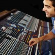 Sound recording studio  - Young guy working with synthesizer - Stock Photo