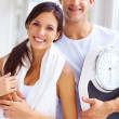 Healthy life - Young couple holding a weight scale - Foto Stock