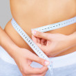 Royalty-Free Stock Photo: Caucasian woman measuring her waistline with a tape