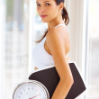 Royalty-Free Stock Photo: An attractive young woman holding weight scale