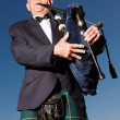 Mature highlander wearing kilt and playing bagpipes - Stock fotografie