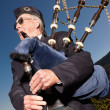 An elderly highlander wearing kilt and playing bagpipes - Stock Photo