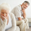 Worried mature man looking at a sad senior woman - Stock Photo