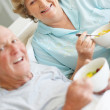 Royalty-Free Stock Photo: Senior couple lying in bed and holding a bowl of fruit salad