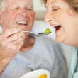 Royalty-Free Stock Photo: Happy senior man feeding fruit salad to a senior mature female
