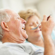 Royalty-Free Stock Photo: Senior man eating a fruit salad with a senior woman
