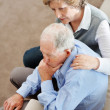 Mature woman comforting senior man while sitting on sofa - Stockfoto