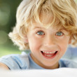 Cheerful little boy with grey eyes smiling - Stock Photo