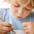 Closeup of an adorable boy holding pen while solving puzzle - Стоковая фотография