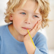 Closeup of an ill boy with thermometer in his mouth - Foto Stock