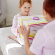 Grandmother giving present to her granddaughter - Stock Photo