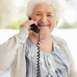 Happy mature woman talking over telephone - Stock Photo