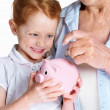 Mature woman with her granddaughter inserting coin in piggybank - Stock Photo