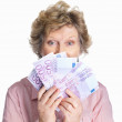 Royalty-Free Stock Photo: Senior female holding cash of five hundred on white background