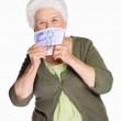 Mature woman smelling paper currency isolated against white - Stock Photo