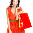 Happy young female holding shopping bags against white - Stock Photo