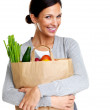 An attractive smiling woman holding a grocery bad on white - Stok fotoğraf