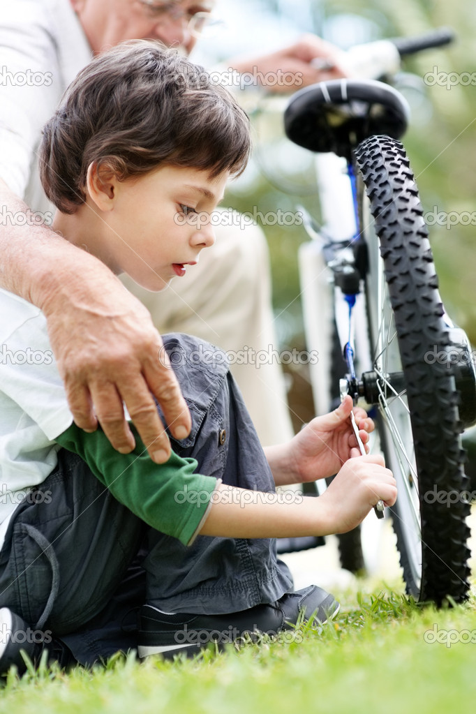 Portrait of little boy repairing a cycle tyre with grandfather - Outdoor — Stock Photo #7711090