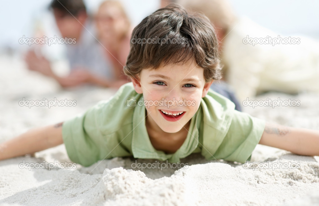 Portrait of happy little boy lying on the beach with his family in background while playing - Outdoors — Stock Photo #7711123
