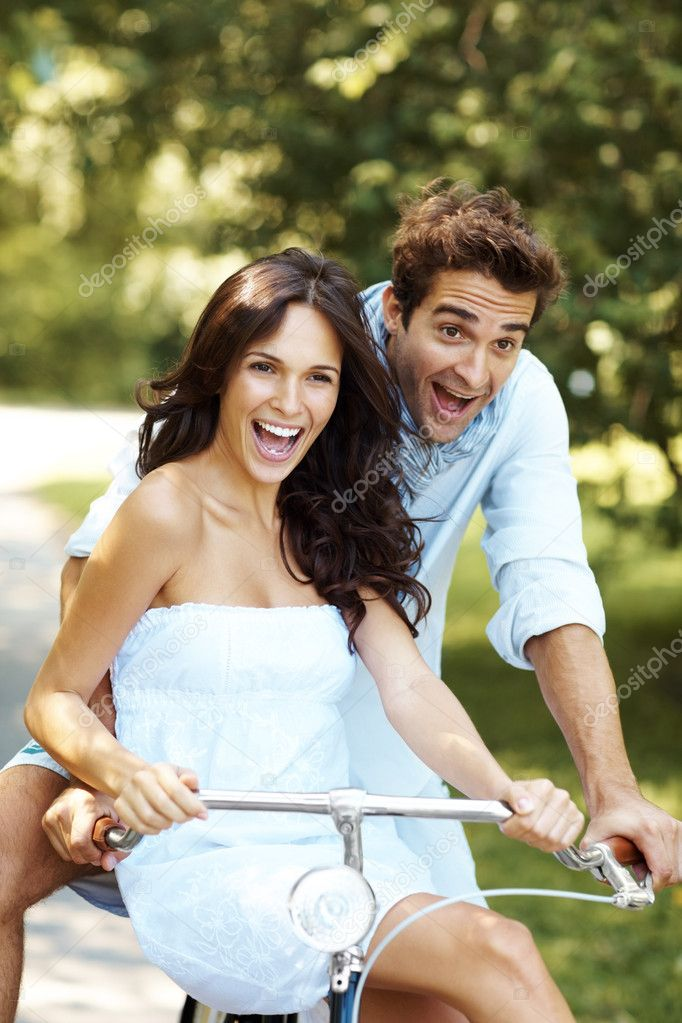 Excited young love couple riding a bicycle in a park - Having fun outdoor — Stock Photo #7711769