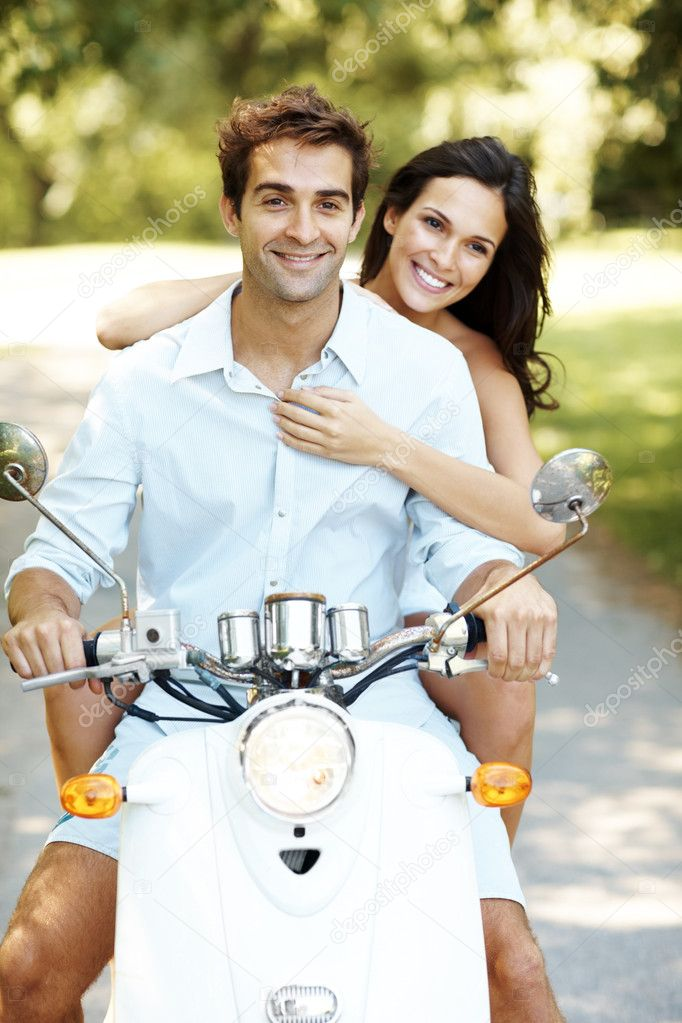 Portrait of beautiful young couple riding on moped in a park — Stock Photo #7711770