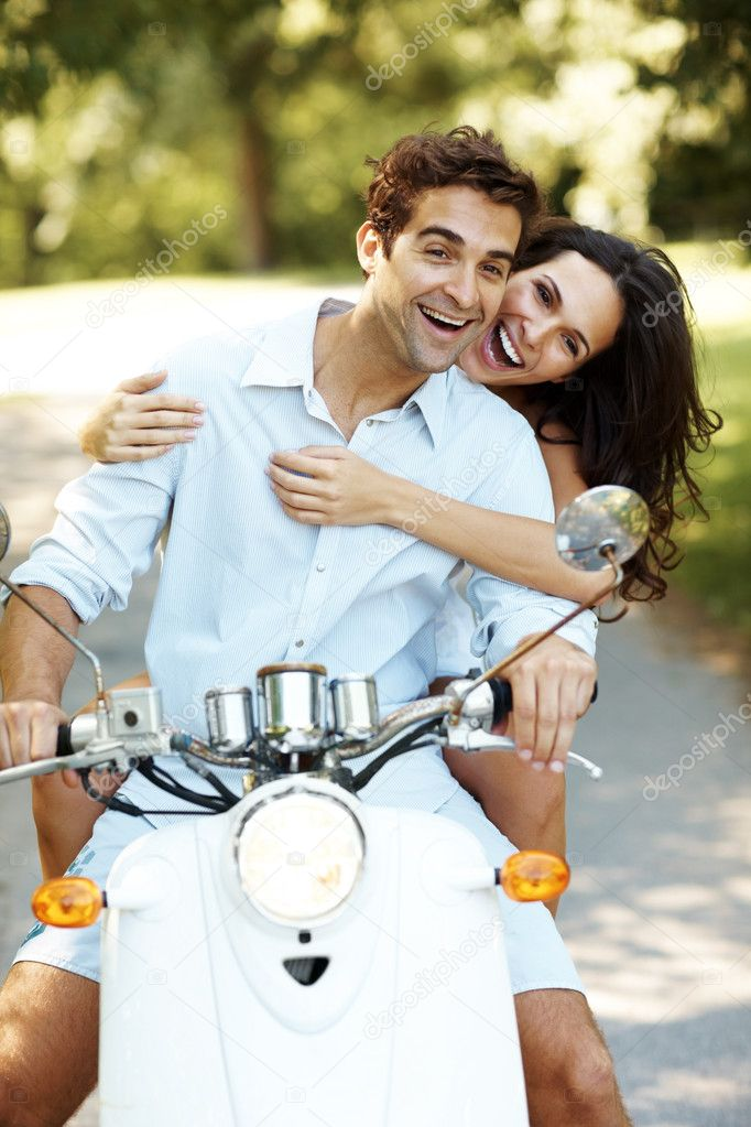 Portrait of love couple on a scooter in a park enjoying themselves — Stock Photo #7711773