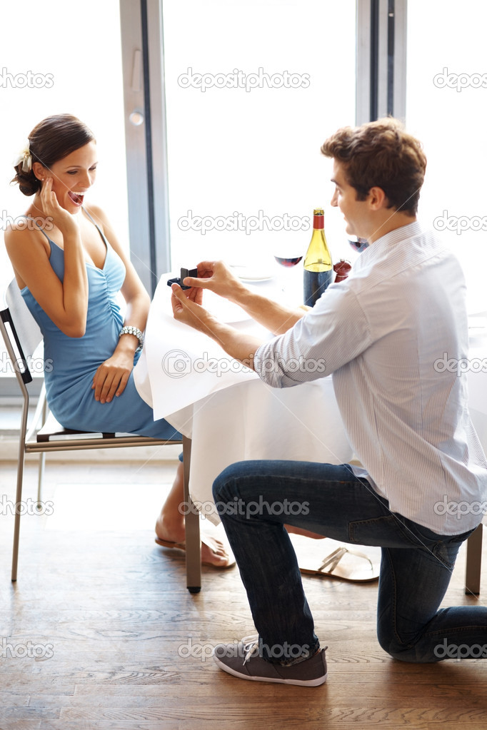 Happy young male proposing with an engagement ring to his surprised girlfriend in a restaurant — Stock Photo #7718594