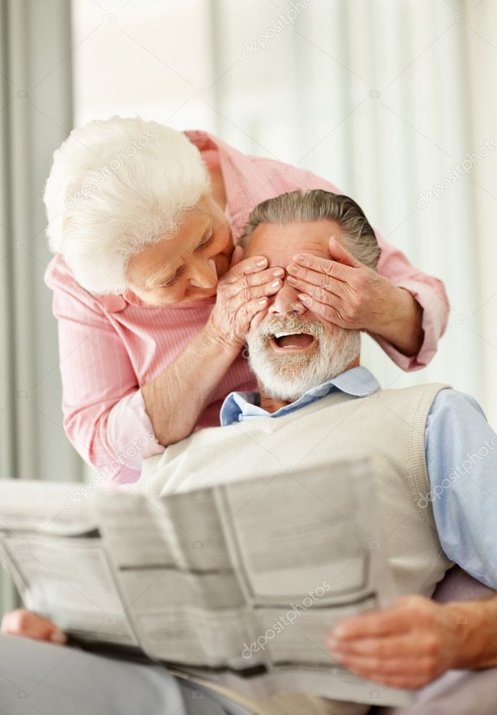 A mature woman covering a senior man's eyes while he's reading a newspaper — Stock Photo #7718752