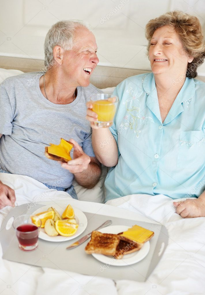 Portrait of a laughing senior couple having fun together during their breakfast  Stock Photo #7718828