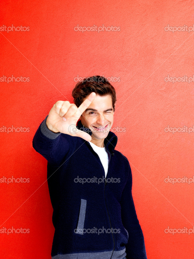 Portrait of trendy young man making a loser gesture with his hand against red background — Stock Photo #7719694