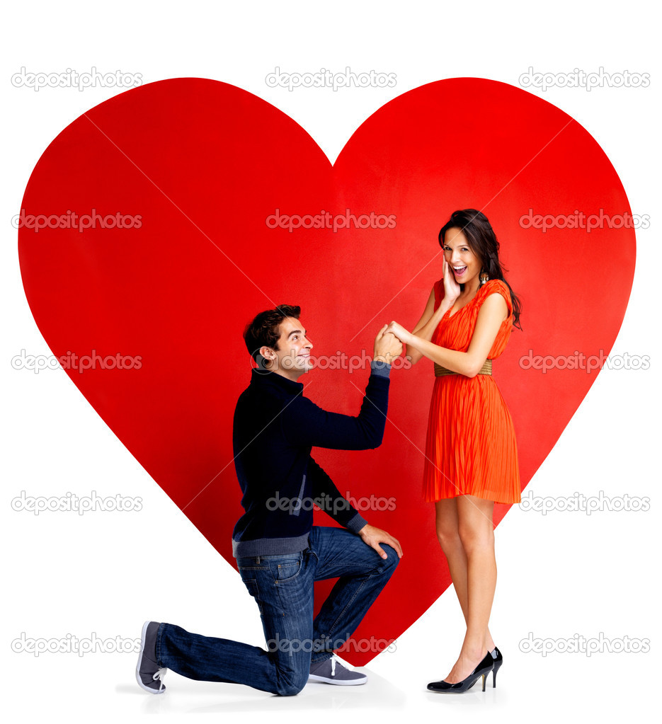 Portrait of handsome young man proposing marriage to a beautiful woman against big red heart on white background — Lizenzfreies Foto #7719699