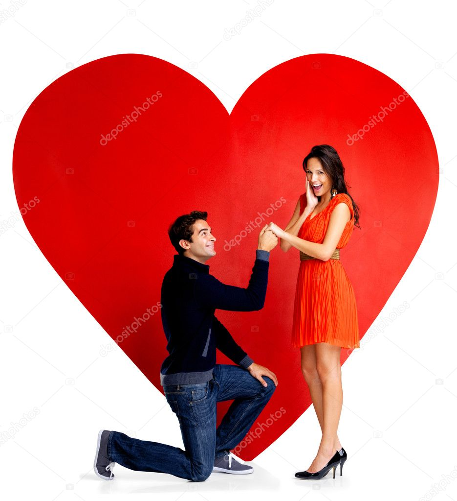 Portrait of handsome young man proposing marriage to a beautiful woman against big red heart on white background — Stockfoto #7719699