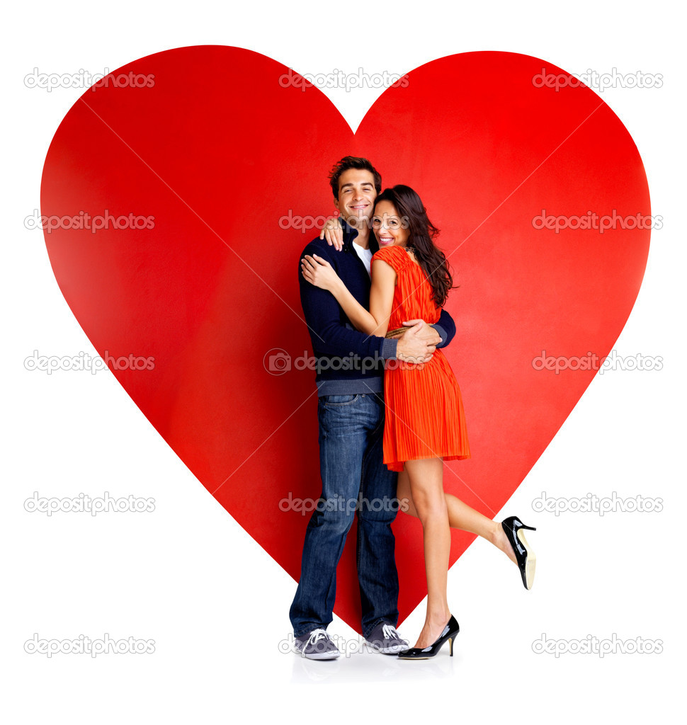 Beautiful young love couple hugging against a big red heart on white background — Stock Photo #7719703