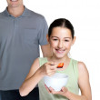 Small girl eating fruit salad standing with her father - Photo