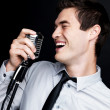 Young male jaz singer singing over dark background - Stock Photo