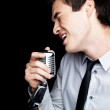 Royalty-Free Stock Photo: Young male star singer singing into old fashioned microphone