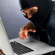 Cyber crime - Male hacker stealing information from laptop - Stock Photo