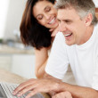 Royalty-Free Stock Photo: Mature couple using laptop computer and smiling