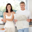 Royalty-Free Stock Photo: Mature man in kitchen with newspaper and wife making breakfast