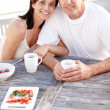 Happy mature couple having fruit salad and coffee together - Stock Photo