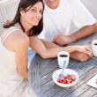 Happy middle aged couple sitting together and having breakfast - Stock Photo
