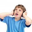 Small boy listening to music on headphones against white - Stock Photo