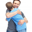 Royalty-Free Stock Photo: Caring young man hugging his son against white background